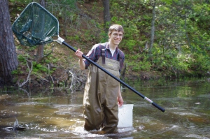 Brad Carlson uses a dipnet to sample a pond community.